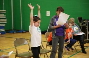 Elm Road student demonstrates a yoga move for P-H-M School Board of Trustees